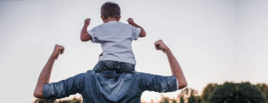 strong child sitting on father's shoulder